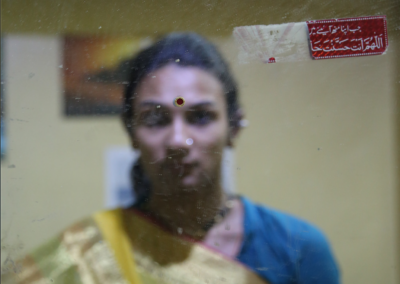 """Shahrukh Faquih: """"To photograph Lakshmi, a Devadasi (assigned male at birth), who is currently transitioning. This is an attempt to visually represent Lakshmi the way she identifies herself. The project is a personal enquiry to understand the gender transitioning of Lakshmi, a Devadasi. It aims to look at Lakshmi's performative lifestyle, the duality she lives everyday, how she is perceived, the choices she makes and the identity she believes in."""""""